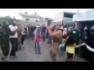 Российский солдат вместе с сирийцами он ликует после возвращения Эль-Кунейтры под контроль Дамаска.
