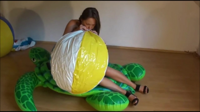 Ragazza sexy in tacchi gonfia un pallone da spiaggia con la bocca