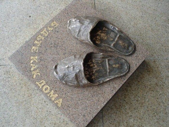 Памятник домашним тапочкам у входа в гостиницу «Томск» (2006)