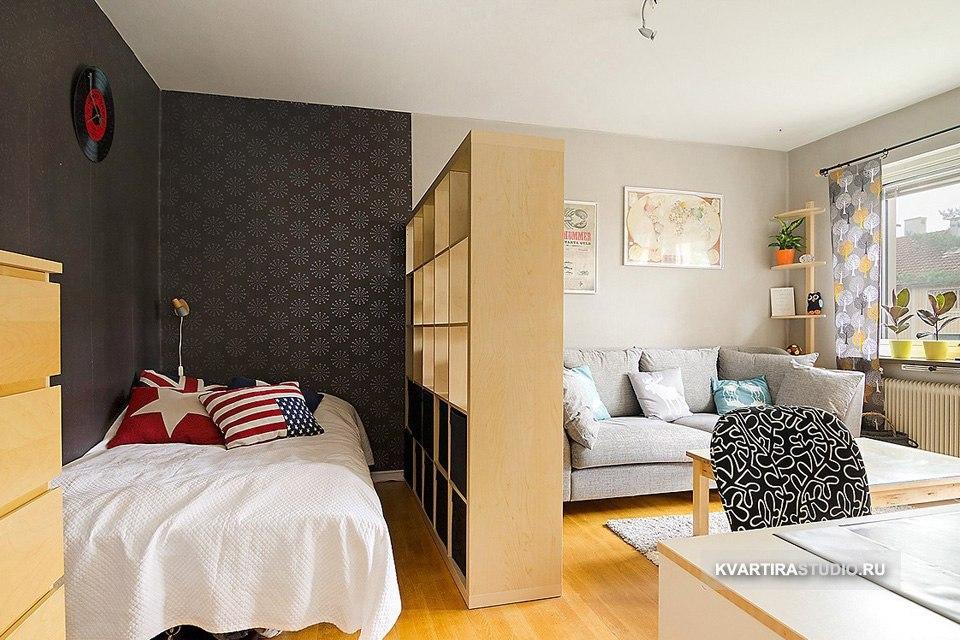 Зонирование комнаты на гостиную и спальню высоким стеллажом под дерево.