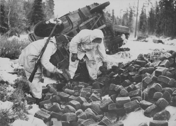 На фото:на обочине дороги Раате-Суомуссалми, финские солдаты собирают буханки хлеба у опрокинутого советского грузовика