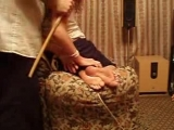 Husband is caning her wife's feet