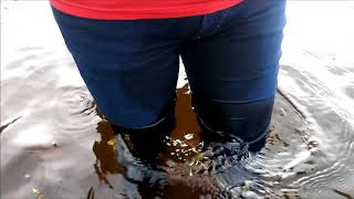 Girl in wet jeans a red turtleneck and boots in deep water 1 MOV 0234 27062018