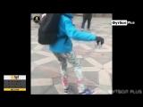 Мальчик кидает мяч между ног прохожих