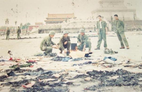 Весёлые китайские солдаты рядом с останками убитых участников протеста.