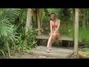 Девушка в красной шляпе гуляет по лесу где-то в тропиках