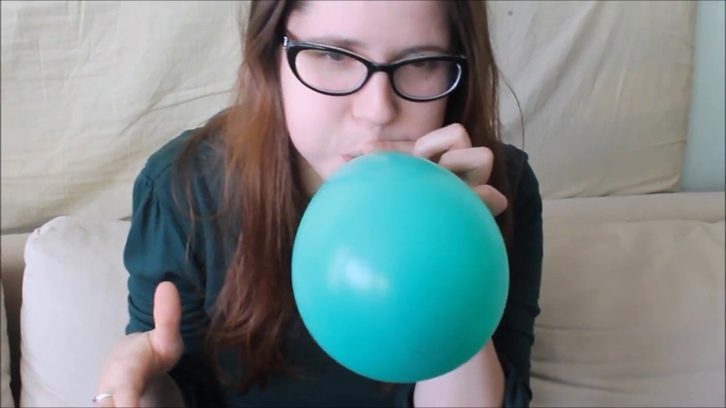 French girl struggles to blow and pop tight teal balloon